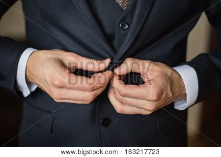 correct button on jacket hands close-up dressing man's style correcting sleeves preparing for the wedding