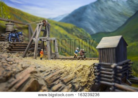 Mining model with tiny people head frame and ore cart tracks. Shallow depth of field with focus on man pushing ore cart.