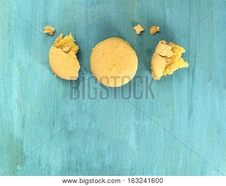 A photo of macarons, shot from above on a vibrant blue background texture, with crumbs and copyspace