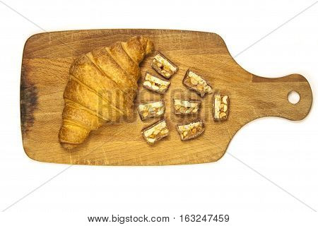 Croissant on a wooden surface. Croissant on a white background. Chopped Snickers with a croissant on a wooden board