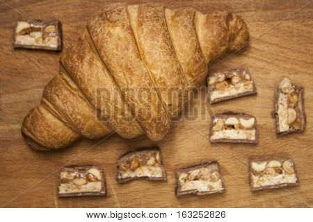 Juicy delicious croissant. Croissant on a wooden surface. Chopped Snickers with a croissant on a wooden board
