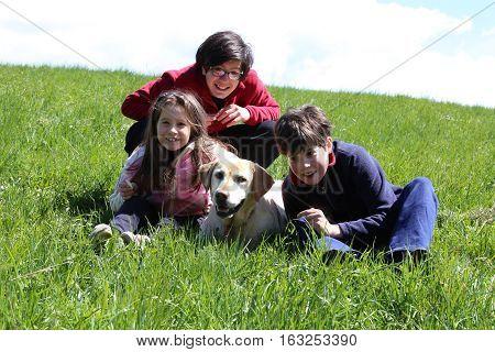Two Boys And A Girl With Labrador Retriever Dog