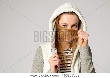 young smiling girl in a hood hides her face in her hair