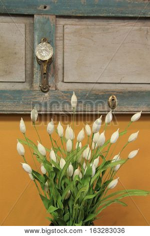 Image of bouquet of silk and paper flowers set against old wood door