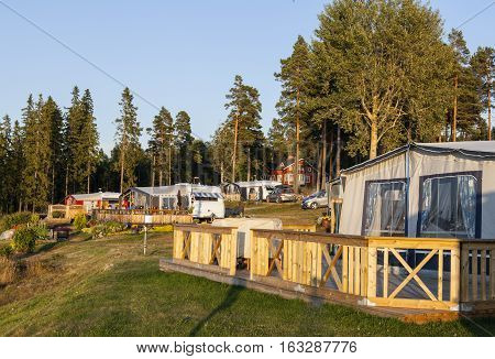 CAMP, SWEDEN ON JULY 26. View of a camping, campsites on July 26, 2013 by the Baltic Sea, Sweden. Cars and caravans, wooden porch. Forest in the background. Editorial use.