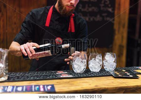 KIEV, UKRAINE - 30 OCTOBER, 2016: Barman festival. Young handsome bartender is making cocktail