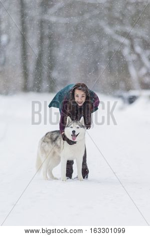 Caucasian Brunette Girl Posing With Her Husky Dog Outside in Winter Forest. Vertical Image Composition