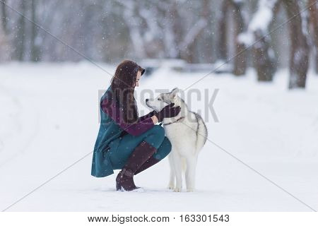 Human and Pet Relationships. Caucasian Brunette Woman Playing with Husky Dog Outdoors in Park Area.Horizontal Image