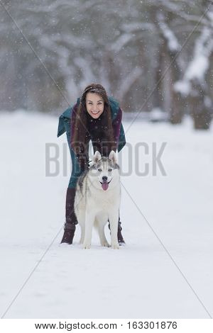 Happy and Smiling Caucasian Brunette Woman Playing with Husky Dog Outdoors in Park. Vertical Image