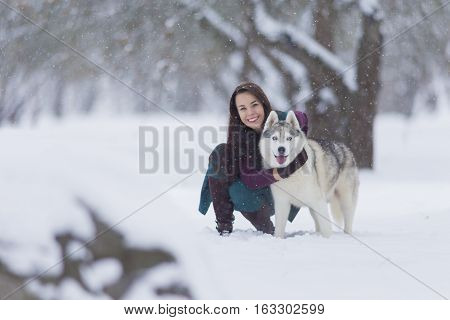 Happy Smiling Caucasian Brunette Woman and Her Husky Dog. Playing Outdoors in Winter White Forest. Horizontal Image