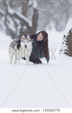 Happy Smiling Caucasian Brunette Woman and Her Husky Dog. Playing Outdoors in Winter White Forest. Vertical Image Composition