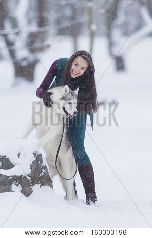 Home Pets Concept and Ideas. Happy Caucasian Brunette Woman and Her Husky Dog. Playing Outdoors in Winter Forest. Vertical Orientation