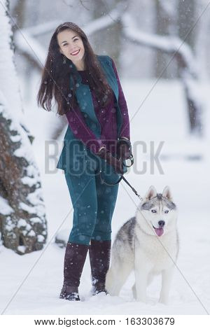 Home Pets Concept and Ideas. Happy Caucasian Brunette Woman and Her Husky Dog. Outdoors in Winter Forest. Vertical Image Composition
