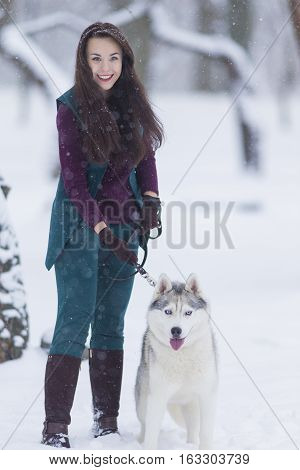 Home Pets Concept and Ideas. Happy Caucasian Brunette Woman and Her Husky Dog. Outdoors in Winter Forest. Vertical Orientation