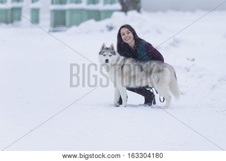 Portrait of Pretty Smiling Woman Hugging Her Husky Dog Outside. Horizontal Image Orientation