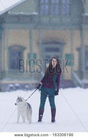 Caucasian Brunette Woman Keeping Her Husky Dog on a Short Leash During a Stroll in Winter Time Outside.Vertical Image Composition