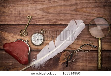Old spectacles near pocket watch feather magnifying glass vintage purse and key on wooden background.