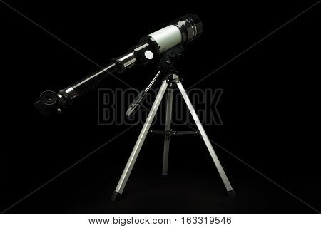 Telescope on the tripod standing isolated on black
