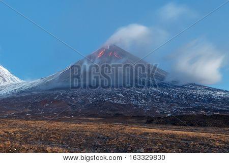 Volcanic landscape of Kamchatka: eruption Klyuchevskoy Volcano lava flows on of volcano; plume of gas steam ash from crater. Kamchatka Peninsula Russia Klyuchevskaya Group of Volcanoes.