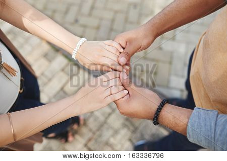 Man holding hands of his fiance, view from above