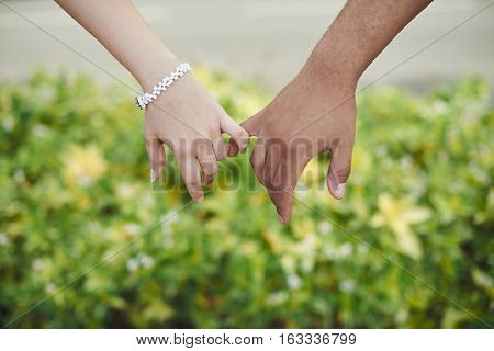 Hands of two people hook their little fingers together