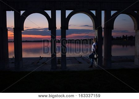 Young woman relaxing on the lake at sunset. Lonely woman enjoy watching sunset over the city lake in Bucharest