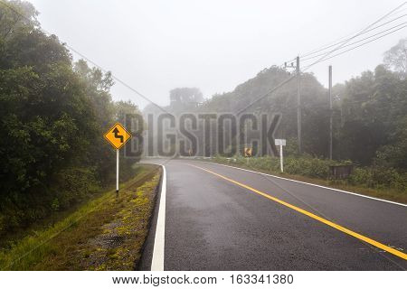 Windy forest road with a curve sign on a foggy day at Doi Inthanon national park Thailand