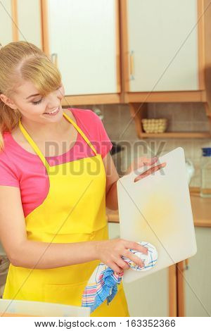 People housework and housekeeping concept. Woman doing the tidying up in kitchen cleaning plastic cutting board with rag sponge