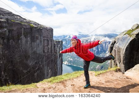Happy tourist having fun on cliff in Norway. Summer sunny day
