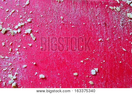 Crumbs in a Grated Red Surface Background