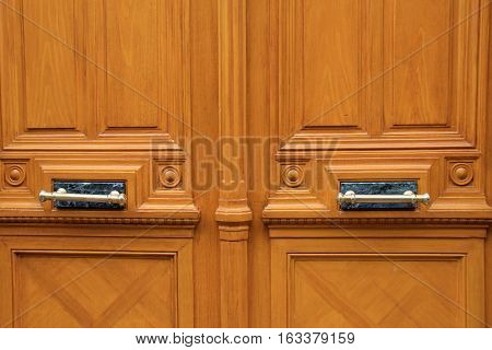 Heavily engraved wood doors with brass and marble hardware
