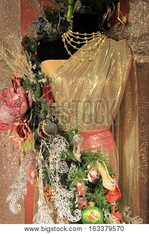 Vertical image of mannequin dressed in party attire, with flowers draped across the shoulder and over the waist.