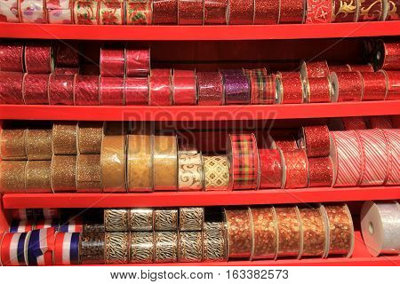 Rows of colorful holiday ribbons set on shelves in store
