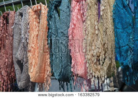 Row of colorful handcrafted scarves hanging from display at local market.