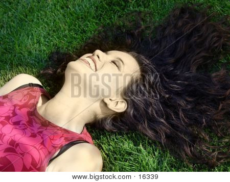 Beautiful Girl Laughing On The Grass