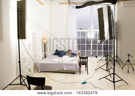 Backstage photo of bedroom during photo session. Many photo equipment for making photos of modern bedroom. Backstage concept.