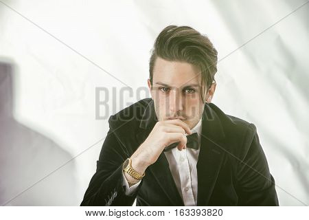 Young businessman confidently posing and looking at camera, wearing suit, on white background