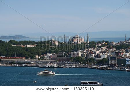 Hagia Sophia and the Blue Mosque, as seen from Galata - Beyoglu - with the Marmara Sea in the Background and the Golden Horn - Bosphorus in the foreground in Istanbul, Turkey.