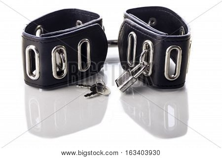 Leather bondage handcuffs for sex fetish and sexual role play. Image isolated against white background with reflection.