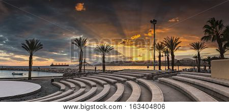 Colorful sunset at the Red Sea; panoramic view from stone amphitheatre on central beach of Eilat - famous resort and recreational city in Israel