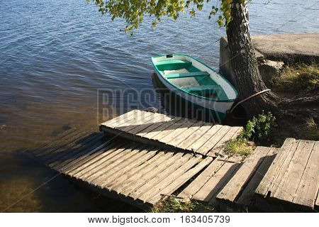 Old boat tied to the shore close up in still water