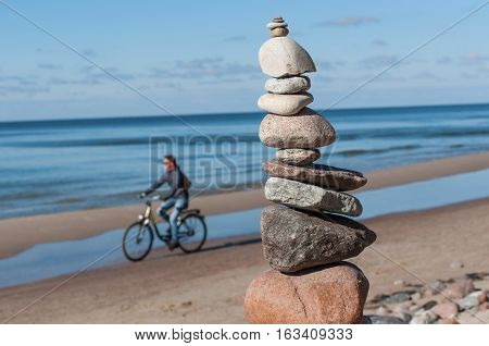 Stones pyramid and cyclist at baltic sea.