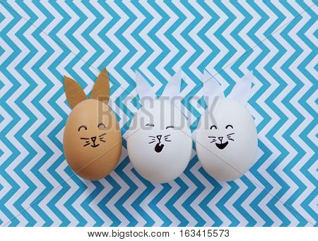 Three brown and white Easter bunny eggs on a blue chevron striped background