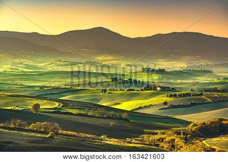 Tuscany countryside misty panorama rolling hills and green fields on sunset. Pisa Italy Europe