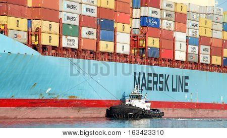 Oakland CA - December 28 2016: Tugboat PATRICIA ANN of the port side of cargo ship MAERSK ANTARES assisting the vessel to maneuver into the Port of Oakland.