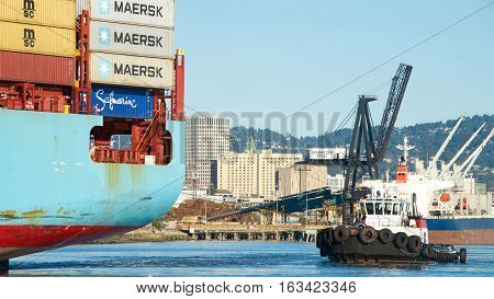 Oakland CA - December 28 2016: Tugboat VETERAN at the stern of cargo ship MAERSK ANTARES assisting the vessel to maneuver into the Port of Oakland.