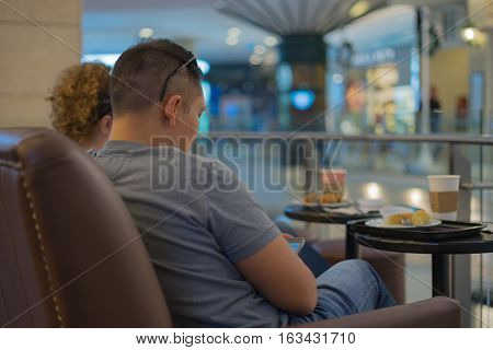 caucasian couple relax on sofa use mobilephone in coffee shop or restaurant in shopping mall chilling / caucasian couple