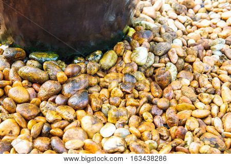 Wet Small pebbles or stone or rock under fountain in garden.