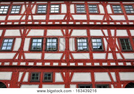 Front view of a typical half-timbered house with red frame white filling and brown windows. Besigheim, Baden-Wurttemberg, Germany.