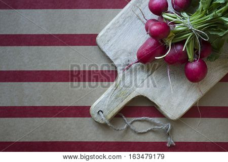 Ripe radish with green Batwa on a wooden board. On striped background.